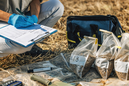 Photo pour Soil Test. Female agronomist taking notes in the field. Environmental protection, organic soil certification, research - image libre de droit