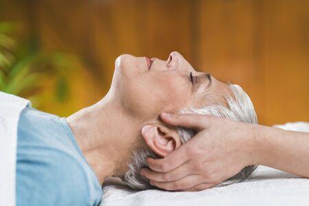 Foto de Marma therapy.  Beautiful senior woman lying on massage table and enjoying Ayurveda Facial treatment. - Imagen libre de derechos