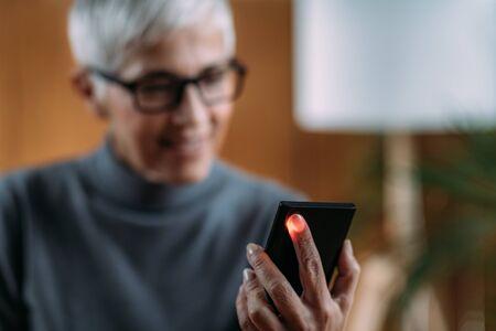Foto de Senior Woman Measuring Pulse or Heart Rate with Smart Phone - Imagen libre de derechos