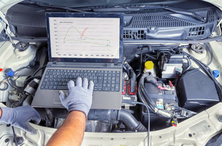 Foto de Professional car mechanic working in auto repair computer service - Imagen libre de derechos