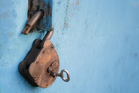 Photo for Old rusty lock with a key on a blue background. - Royalty Free Image