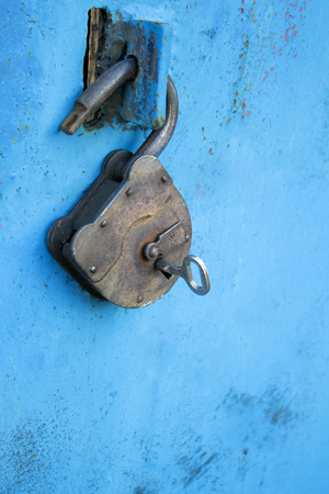 Photo for Old rusty lock with a key on a blue background - Royalty Free Image