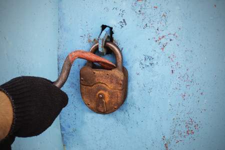 Photo for The thief opens the old lock. - Royalty Free Image