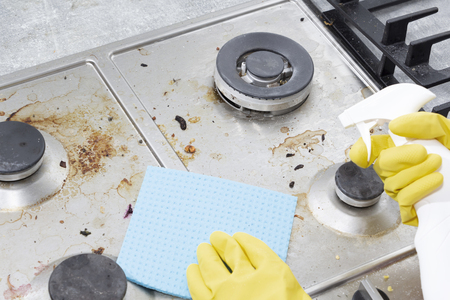 Photo pour Cleaning a gas stove with kitchen utensils, household concepts, or hygiene and cleaning - image libre de droit