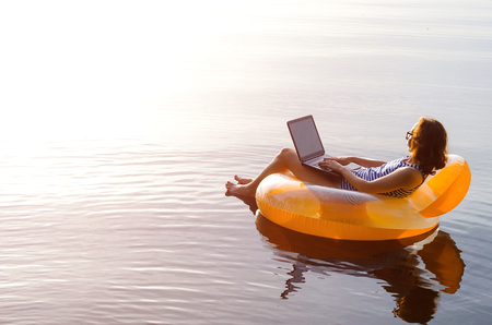 Foto de Business woman working on a laptop in an inflatable ring in the water, a copy of the free space. Workaholic, work on vacation. - Imagen libre de derechos