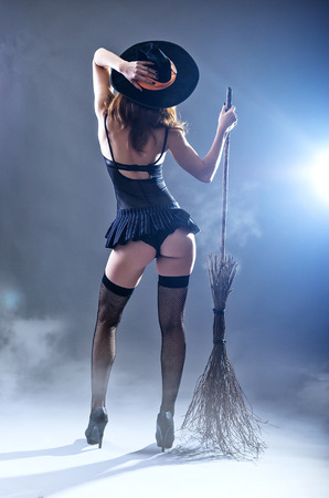Photo for Background to Halloween, sexy woman in a witch costume with a broom, view from the back. Young woman in a carnival costume of a witch on a gray background. - Royalty Free Image