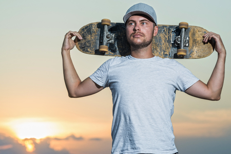 Photo for Portrait of a stylish skateboarder in the background of a bright sunset. Active lifestyle. - Royalty Free Image