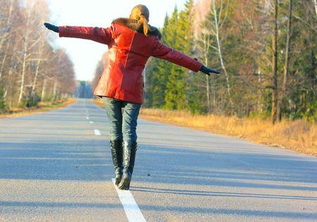 Foto de Young woman walking on asphalt road - Imagen libre de derechos