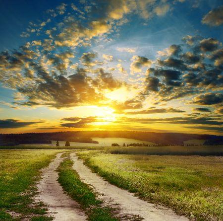 Photo pour Road in field over sunset - image libre de droit