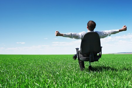 Photo pour Young businessman sitting on chair in green field - image libre de droit