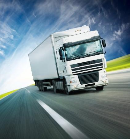 White truck on asphalt blurry road