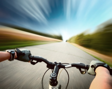 Rider driving bicycle on an asphalt road. Motion blurred background mural
