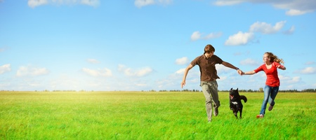 Young happy lovers runnung with a dog on meadow with green grass and blue sky