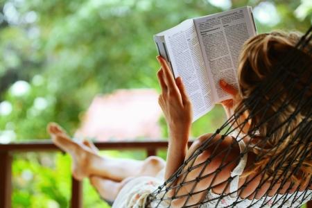 Foto de Young woman reading a book lying in a hammock - Imagen libre de derechos