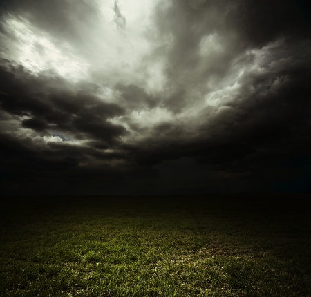 Dark storm clouds over meadow with green grass