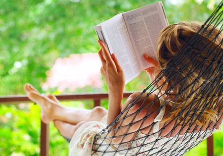 Photo pour Young woman lying in hammock in a garden and reading a book. Shallow DOF. Focus on a left shoulder - image libre de droit