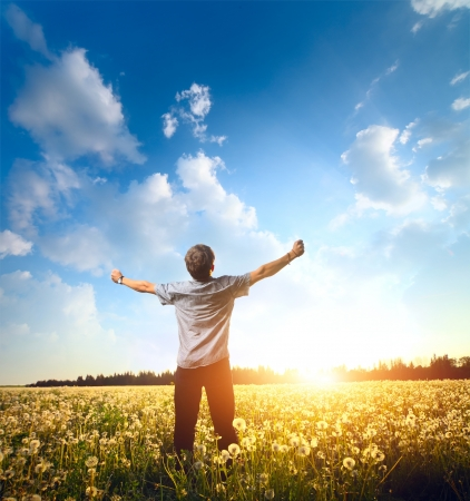 Photo pour Young man standing on a meadow with raised hands and looking to a sky - image libre de droit