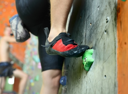Young man's foot climbing indoor wall