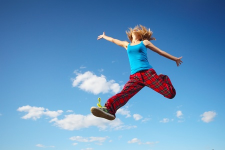 Photo for Young happy woman jumping on blue sky background - Royalty Free Image