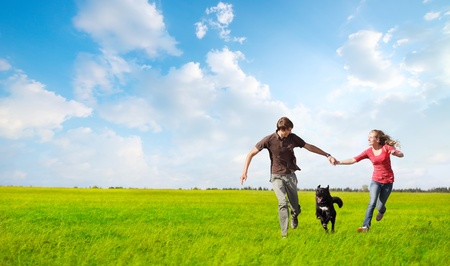 Young happy couple running on a green meadow with a black dog