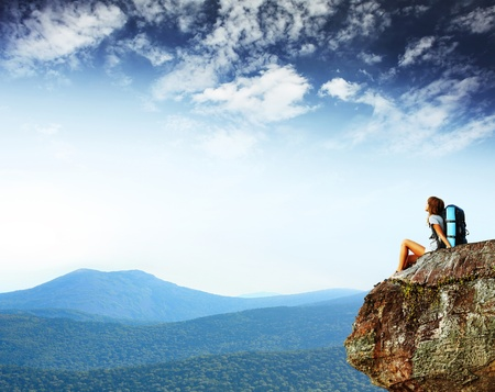 Foto de Young woman with backpack sitting on cliff's edge and looking to a sky - Imagen libre de derechos