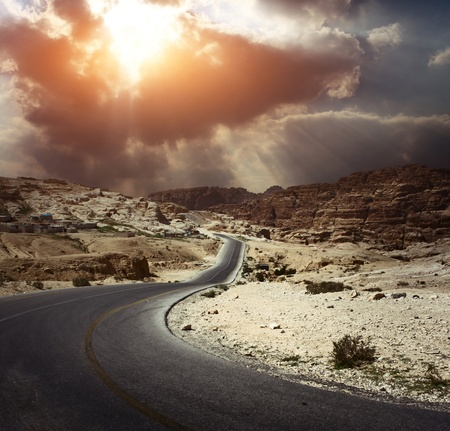 Photo pour Asphalt road in a desert with dark cloudy sky on the background - image libre de droit
