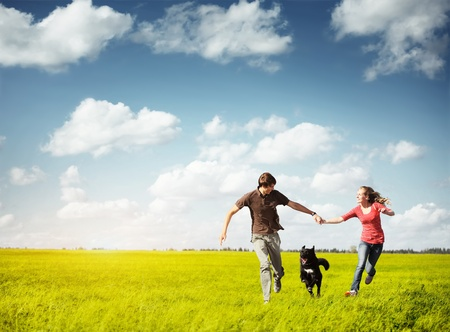 Young happy couple runnig on a green meadow with a dog