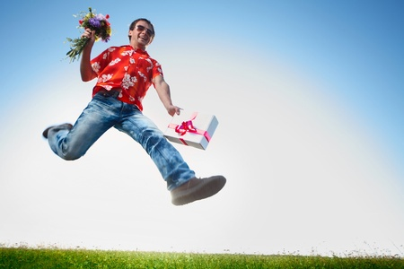 Young happy man in sunglasses jumping with flowers and gift box on blue sky background