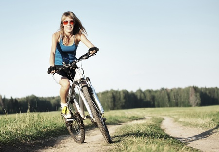 Photo pour Young woman riding on a bicycle on a countryside road - image libre de droit