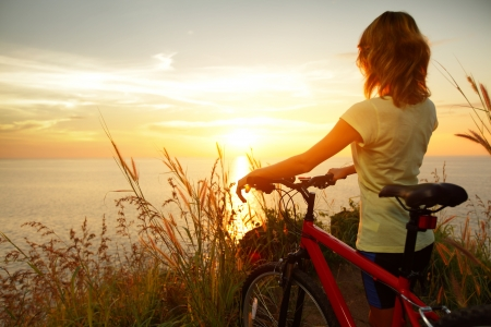 Foto de Young lady standing with bicycle on a sea coast and enjoying sunset - Imagen libre de derechos