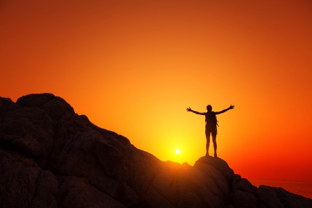 Photo pour Young tourist with backpack standing on a rock and enjoying sunset - image libre de droit