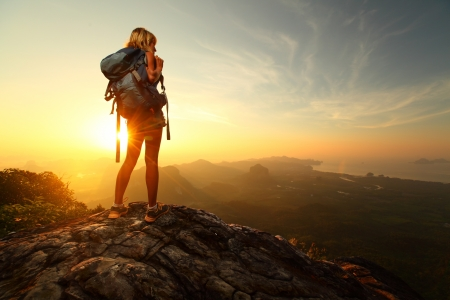 Hiker with backpack relaxing on top of a mountain and enjoying sunrise