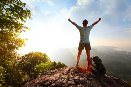 Hiker with backpack standing on top of a mountain with raised hands