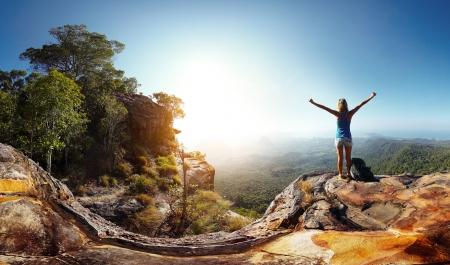 Foto de Hiker with backpack enjoying valley view from top of a mountain - Imagen libre de derechos