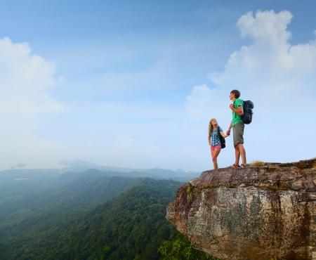 Foto de Two hikers standing on top of a mountain and enjoying valley view - Imagen libre de derechos