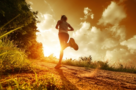 Photo pour Young lady running on a rural road during sunset - image libre de droit
