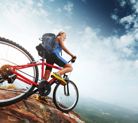 Foto de Female tourist with backpack and bicycle enjoying valley view from top of a mountain - Imagen libre de derechos