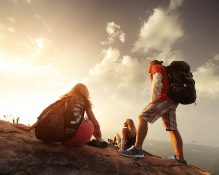 Photo pour Group of hikers relaxing on top of a mountain and enjoying sunrise - image libre de droit