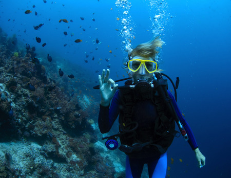 Photo for Underwater shoot of a woman diving with scuba by coral reef and showing ok signal - Royalty Free Image