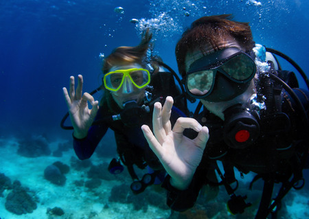 Photo for Underwater shoot of a couple diving with scuba and showing ok signal. Focus on a man's hand - Royalty Free Image