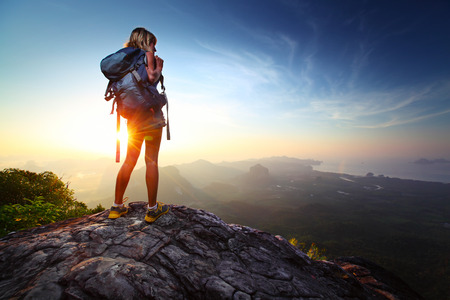 Foto de Young lady hiker standing with backpack on top of a mountain and enjoying sunrise - Imagen libre de derechos