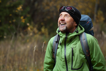 Photo pour Happy mature backpacker in an autumn forest - image libre de droit