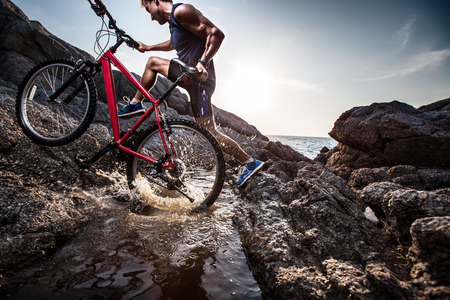 Photo for Athlete crossing rocky terrain with water barrier with his bicycle - Royalty Free Image