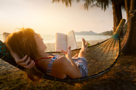 Foto de Young lady reading a book in hammock on a beach at sunset - Imagen libre de derechos