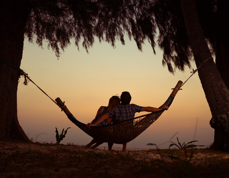 Photo pour Young couple relaxing in the hammock at sunset - image libre de droit