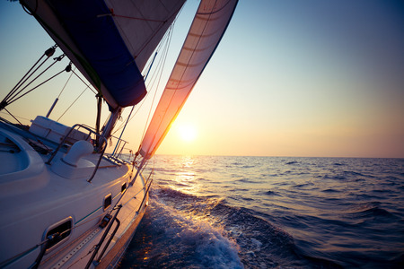 Photo pour Sail boat gliding in open sea at sunset - image libre de droit