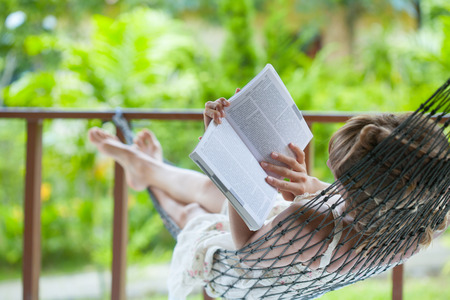 Photo pour Lady reading the book in the hammock - image libre de droit