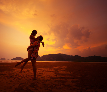Photo pour Young couple relaxing on a tropical beach at sunset - image libre de droit