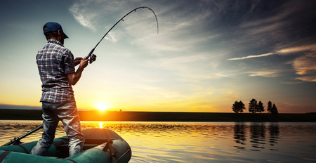 Photo pour Mature man fishing from the boat on the pond at sunset - image libre de droit
