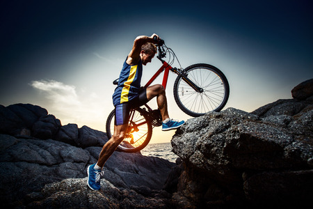 Photo for Bicycle rider crossing rocky terrain at sunset - Royalty Free Image